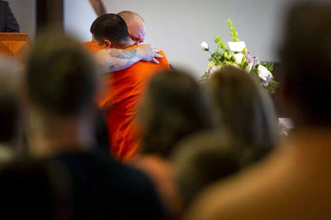 A friend hugs David Jaramillo, father of Michael Jaramillo who was killed on the Raging River ride at Adventureland, during his funeral at Corinthian Baptist Church Saturday, July 17, 2021 in Des Moines, Iowa. Michael Jaramillo died after an amusement ride capsized. (Brian Powers/The Des Moines Register via AP)