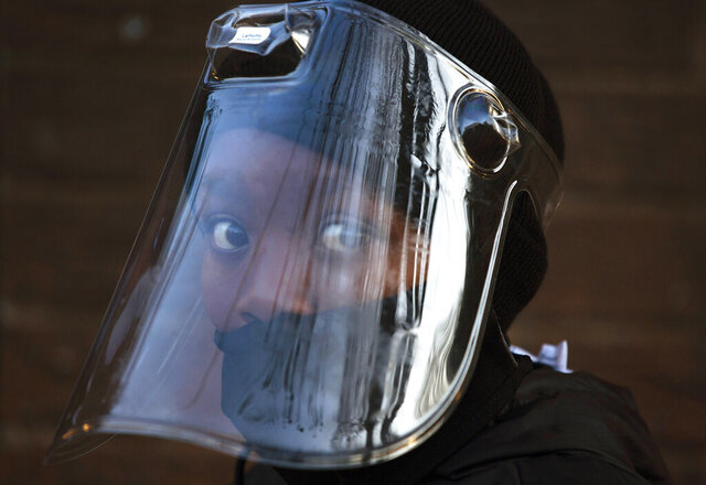 """FILE — In this Aug. 24, 2020 file photo, a student, wearing a face mask and shield, returns to the Melpark Primary School in Johannesburg after several months of lockdown. Ordinarily, South Africa sees widespread influenza during the winter months, but this year almost none have been found — something unprecedented. School closures, limited public gatherings and calls to wear masks and wash hands have """"knocked down the flu,"""" said Dr. Cheryl Cohen, head of the institute's respiratory program. (AP Photo/Denis Farrell, File)"""
