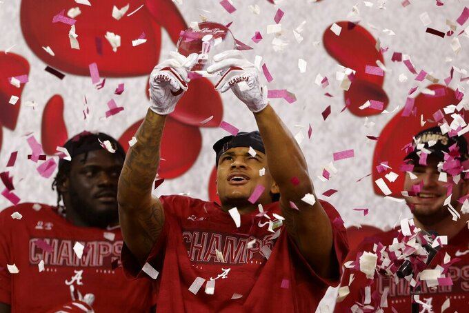 Alabama wide receiver DeVonta Smith holds up his most outstanding offensive player trophy after their 31-14 win against Notre Dame in the Rose Bowl NCAA college football game in Arlington, Texas, Friday, Jan. 1, 2021. (AP Photo/Ron Jenkins)