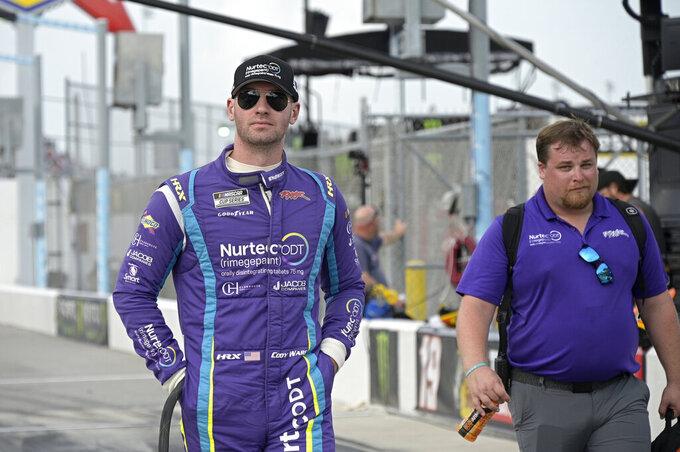 Driver Cody Ware, left, walks to his car on pit road before a NASCAR Cup Series auto race at Daytona International Speedway, Saturday, Aug. 28, 2021, in Daytona Beach, Fla. (AP Photo/Phelan M. Ebenhack)
