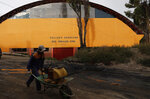 In this Jan. 20, 2020 photo, a man pushes his wheelbarrow in front of a sports coliseum named after Bolivia's former President Evo Morales, in Achocalla, Bolivia. During his administration Morales would often personally inaugurate the fields and venues, playing a soccer game against local officials. (AP Photo/Juan Karita)