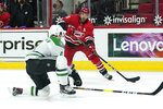 Carolina Hurricanes left wing Jordan Martinook (48) shoots while Dallas Stars defenseman Miro Heiskanen (4) defends during the second period of an NHL hockey game in Raleigh, N.C., Sunday, April 4, 2021. (AP Photo/Gerry Broome)