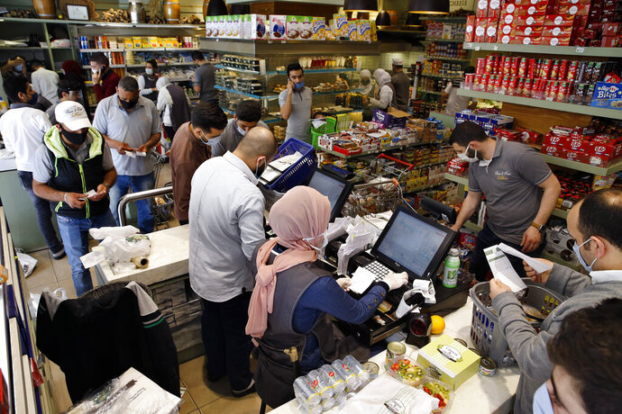 People shop at a supermarket as they begin to stock up on provisions, in Beirut, Lebanon, Wednesday, May 13, 2020. Lebanese rushed to food stores to stock up on vegetables and basic items, hours before the government was to reinstate a four-day nationwide lockdown on Wednesday, following a spike in reported coronavirus cases. (AP Photo/Bilal Hussein)