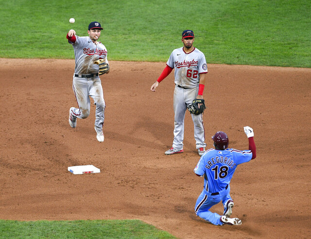 Washington Nationals' Trea Turner, left, turns a double play on a ball hit by Philadelphia Phillies' Jean Segura as Phillies' Didi Gregorius (18) slides into second base during the fifth inning of a baseball game, Thursday, Sept. 3, 2020, in Philadelphia. (AP Photo/Derik Hamilton)