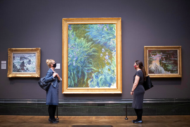 FILE - In this Saturday, July 4, 2020 file photo, visitors wearing PPE stand apart as they view Irises, 1914-17, by Claude Monet, a the National Portrait Gallery, London, as it prepares to reopen following the easing of coronavirus lockdown restrictions across England. The British government has announced more than 1.5 billion pounds (almost $2 billion) to help the country's renowned arts and cultural institutions recover from the coronavirus pandemic, after some theaters and music venues warned that without support they might never open again. (Victoria Jones/PA via AP, File)