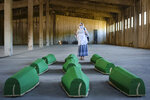 A woman prays next to victims' coffins inside the former UN base in Potocari, near Srebrenica, Bosnia, Friday, July 10, 2020. Nine newly found and identified men and boys will be laid to rest when Bosnians commemorate on Saturday 25 years since more than 8,000 Bosnian Muslims perished in 10 days of slaughter, after Srebrenica was overrun by Bosnian Serb forces during the closing months of the country's 1992-95 fratricidal war, in Europe's worst post-WWII massacre. (AP Photo/Kemal Softic)