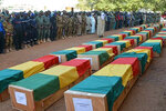 In this photo made available from the Mali Army, showing coffins being honoured during a funeral ceremony in Gao, Mali, Wednesday Nov. 20, 2019.  The Mali Defense Ministry held a funeral for the 30 soldiers killed in a Monday attack on an army patrol by extremists near the border with Niger. (Mali Army via AP)