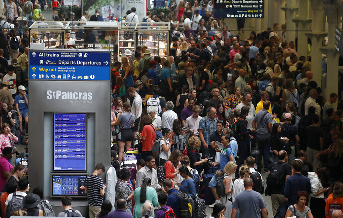 People wait at the St Pancras International train station to board the Eurostar in London, Friday, July 26, 2019.  A power outage at one of France's busiest train stations is disrupting travel on the Eurostar to and from London and other routes around the region. (AP Photo/Frank Augstein)