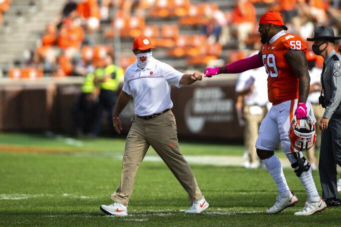Clemson head coach Dabo Swinney fist bumps defensive tackle Jordan Williams (59) after an NCAA college football game against Syracuse in Clemson, S.C., on Saturday, Oct. 24, 2020. (Ken Ruinard/Pool Photo via AP)