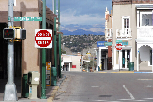 An empty street and closed stores are shown at a central plaza and shopping district amid a public health order that has closed down most retail stores and suspended dine-in restaurant service in Santa Fe, N.M., Friday, March 27, 2020. New Mexico Cabinet Secretary for Tourism Jen Schroer says the state's tourism industry will continue to suffer amid COVID-19 restrictions and vowed the state will do what it can to help hotels, tourist spots, and businesses recover once restrictions are lifted. (AP Photo/Morgan Lee)
