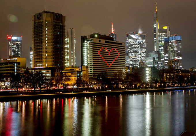 FILE - In this Dec. 10, 2020 file photo, a hotel has switched on the lights in some rooms to form a heart near the buildings of the banking district in in Frankfurt, Germany. More than 50,000 people have died after contracting COVID-19 in Germany, a number that has risen swiftly over recent weeks as the country has struggled to bring down infection figures. (AP Photo/Michael Probst, File)