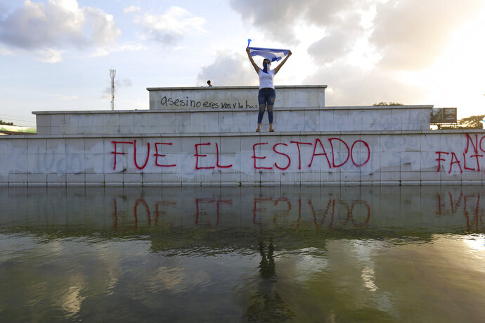 FILE - In this June 1, 2018 file photo, a masked protestor holds up a Nicaraguan flag above the Spanish graffiti phrase: