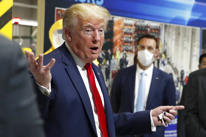 President Donald Trump holds a face mask in his left hand as speaks during a tour of Ford's Rawsonville Components Plant that has been converted to making personal protection and medical equipment, Thursday, May 21, 2020, in Ypsilanti, Mich. (AP Photo/Alex Brandon)