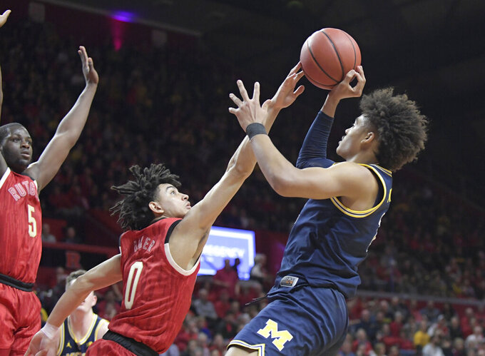 Rutgers guard Geo Baker (0) attempts to block a shot by Michigan guard Jordan Poole (2) during the first half of an NCAA college basketball game Tuesday, Feb. 5, 2019, in Piscataway, N.J. (AP Photo/Bill Kostroun)