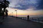 In this Saturday, March 21, 2020 photo, a man takes pictures of the sunset on Beirut's Mediterranean seaside corniche, which is almost empty of residents and tourists in Beirut, Lebanon. The COVID-19 pandemic has managed to do what various wars could not: Close bars, restaurants and entertainment spots across the tiny Mediterranean country. Even Lebanon's corniche, usually dotted with people doing their morning exercise, coffee vans and corn on the cob sellers, is now empty. (AP Photo/Bilal Hussein)
