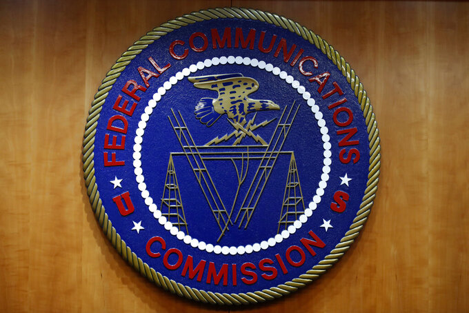 FILE - In this Dec. 14, 2017, file photo, the seal of the Federal Communications Commission (FCC) is seen before an FCC meeting to vote on net neutrality in Washington. The Senate has narrowly approved President Donald Trump's lame-duck nominee, Nathan Simington, on Tuesday, Dec. 8, 2020, to become a member of the Federal Communications Commission. (AP Photo/Jacquelyn Martin, File)