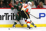 Minnesota Wild center Ryan Donato (6) is stopped from getting the puck by Calgary Flames defenseman Travis Hamonic (24) in the third period during an NHL hockey game Sunday, Jan. 5, 2020, in St. Paul, Minn. The Flames defeated the Wild 5-4 in the shoot out. (AP Photo/Andy Clayton-King)