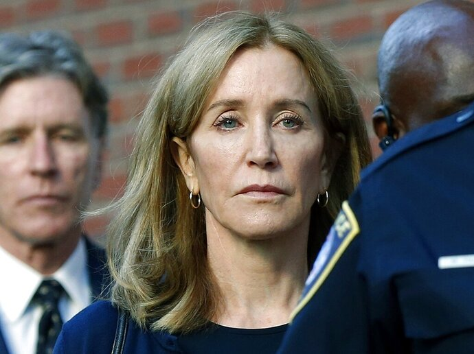 FILE - In this Sept. 13, 2019 file photo, actress Felicity Huffman leaves federal court in Boston with her brother Moore Huffman Jr., left, after she was sentenced in a nationwide college admissions bribery scandal. Huffman was sentenced to 14 days in federal prison in Dublin, Calif., but was released early after serving 10 days. (AP Photo/Michael Dwyer, File)
