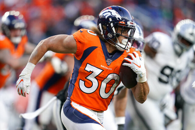 FILE - In this Dec. 29, 2019, file photo, Denver Broncos running back Phillip Lindsay runs with the ball during the second half of an NFL football game against the Oakland Raiders, in Denver. Lindsay insists his noticeably bigger biceps have nothing to do with the Broncos' signing of free agent Melvin Gordon.