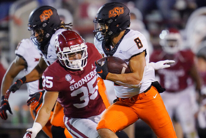Oklahoma State wide receiver Braydon Johnson (8) carries past Oklahoma linebacker Shane Whitter (35) during the second half of an NCAA college football game in Norman, Okla., Saturday, Nov. 21, 2020. (AP Photo/Sue Ogrocki)