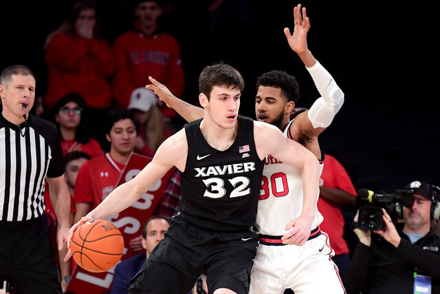 Xavier's Zach Freemantle (32) tries to get around the defense of St. John's LJ Figueroa during an NCAA college basketball game in New York on Monday, Feb 17, 2020. (Steven Ryan/Newsday via AP)