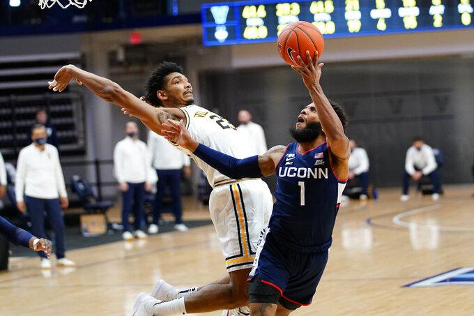 Connecticut's R.J. Cole (1) goes up for a shot against Villanova's Jermaine Samuels (23) during the second half of an NCAA college basketball game, Saturday, Feb. 20, 2021, in Villanova, Pa. (AP Photo/Matt Slocum)