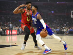 Los Angeles Clippers forward Paul George, right, drives the ball to the basket while Atlanta Hawks forward De'Andre Hunter defends during the first half of an NBA basketball game in Los Angeles, Saturday, Nov. 16, 2019. (AP Photo/Kelvin Kuo)