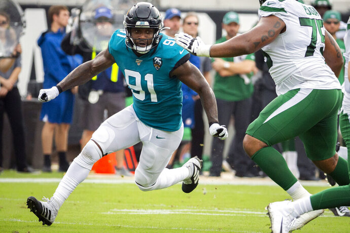 FILE - In this Oct. 27, 2019, file photo, Jacksonville Jaguars defensive end Yannick Ngakoue (91) rushes New York Jets quarterback Sam Darnold (14) during the first half of an NFL football game, in Jacksonville, Fla. When or if Yannick Ngakoue returns to the Jacksonville Jaguars, the disgruntled defensive end will need several introductions. The Jaguars have been forced to revamp their defensive line during the first two weeks of training camp, and they don't appear done. (AP Photo/Stephen B. Morton, File)