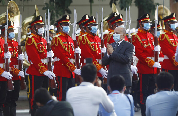 Cambodia's King Norodom Sihamoni, center, reviews the honorary troop during the country's 67th Independence Day celebration, in Phnom Penh, Cambodia, Monday, Nov. 9, 2020. (AP Photo/Heng Sinith)