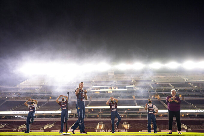 Texas A&M University Head Yell Leader Keller Cox, center, address the crows as part of the first Midnight Yell Practice this season in Kyle Field, College Station, Texas early Saturday, Sept. 26, 2020. Due to Coronavirus restrictions, the Texas A&M Band were the only crowd allowed in the normally packed stands for the traditional game day event in College Station, Texas. (Sam Craft/Pool Photo via AP)