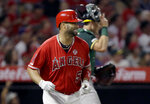 Los Angeles Angels designated hitter Albert Pujols, left, smiles after hitting an RBI sacrifice fly to left field to score David Fletcher, with Oakland Athletics catcher Sean Murphy, right, watching during the fifth inning of a baseball game in Anaheim, Calif., Tuesday, Sept. 24, 2019. (AP Photo/Alex Gallardo)