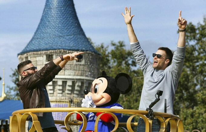 Super Bowl MVP Julian Edelman and Patriots quarterback Tom Brady, right, celebrate with Mickey Mouse in the Super Bowl victory parade in the Magic Kingdom, at Walt Disney World, in Lake Buena Vista, Fla., Monday, Feb. 4, 2019. (Joe Burbank/Orlando Sentinel via AP)