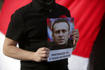 FILE - In this March 6, 2021, file photo, a demonstrator holds a picture of Russian jailed opposition leader Alexei Navalny during a protest demanding freedom for political prisoners organized by a Belorussian cultural association, in Lisbon. The mayor of Lisbon is under fire after admitting that municipal employees shared with Russian officials personal details of at least three Lisbon-based dissidents who organized protests in support of Navalny. (AP Photo/Armando Franca)