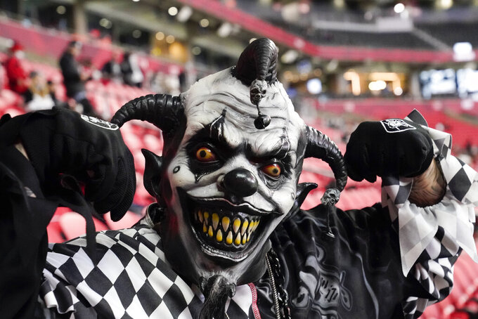 A Las Vegas Raiders fan poses for a photo before the first half of an NFL football game between the Atlanta Falcons and the Las Vegas Raiders, Sunday, Nov. 29, 2020, in Atlanta. (AP Photo/Brynn Anderson)