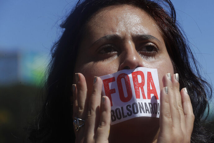 A teacher covers her mouth with a sticker that reads in Portuguese