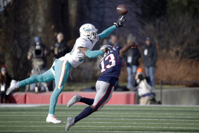 Miami Dolphins defensive back Nate Brooks, left, breaks up a pass intended for New England Patriots wide receiver Phillip Dorsett, but was penalized for pass interference, in the first half of an NFL football game, Sunday, Dec. 29, 2019, in Foxborough, Mass. (AP Photo/Elise Amendola)