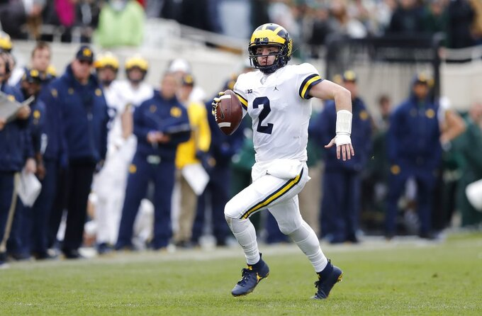 Michigan quarterback Shea Patterson scrambles during the first half of an NCAA college football game against Michigan State, Saturday, Oct. 20, 2018, in East Lansing, Mich. (AP Photo/Carlos Osorio)