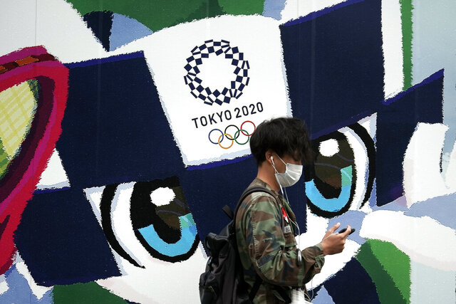 A man walks in front of an advertisement for the Tokyo 2020 Olympics Thursday, Oct. 8, 2020, in Tokyo. Typhoon Chan-hom is approaching Japan's main island with authorities warning of strong winds and torrential rains. (AP Photo/Eugene Hoshiko)