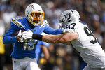 Los Angeles Chargers wide receiver Keenan Allen, left, is tackled by by Oakland Raiders defensive end Josh Mauro during the first half of an NFL football game Sunday, Dec. 22, 2019, in Carson, Calif. (AP Photo/Kelvin Kuo)