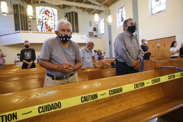 Faithful pray while yellow tape enforces social distance amid the coronavirus pandemic at the San Gabriel Mission Sunday, July 12, 2020, in San Gabriel, Calif. A fire on Saturday destroyed the rooftop and most of the interior of the nearly 250-year-old California church that was undergoing renovation. (AP Photo/Marcio Jose Sanchez)