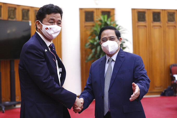 Vietnamese Prime Minister Pham Minh Chinh, right, and Japanese Defense Minister Nobuo Kishi shake hands in Hanoi, Vietnam Sunday, Sept. 12, 2021. Japan can now give defense equipment and technology to Vietnam under an agreement signed Saturday, as the two countries step up their military cooperation amid worries about China's growing military influence. (Duong Van Giang/VNA via AP)