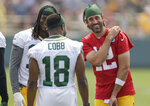 FILE - Green Bay Packers' quarterback Aaron Rodgers (12) shares a laugh with wide receivers Davante Adams (17) and Randall Cobb (18) during NFL football training camp in Green Bay, Wisc., in this Saturday, July 31, 2021, file photo. Green Bay Packers wideout Davante Adams says the addition of veteran Randall Cobb has made it easier to provide leadership to the team's younger receivers. But it's also made it tougher for those other receivers to make the 53-man roster.(AP Photo/Matt Ludtke, File)