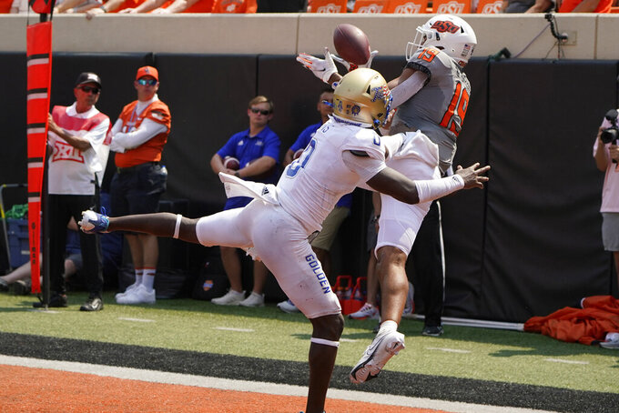 Oklahoma State wide receiver Bryson Green (19) catches a touchdown pass in front of Tulsa cornerback Tyon Davis (0) in the second half of an NCAA college football game, Saturday, Sept. 11, 2021, in Stillwater, Okla. (AP Photo/Sue Ogrocki)