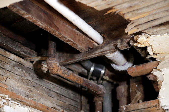 FILE - In this Nov. 8, 2018, file photo, a lead pipe, left, is seen in a hole the kitchen ceiling in the home of Desmond Odom, in Newark, N.J. The Trump administration is proposing a rewrite of rules for dealing with lead pipes contaminating drinking water, but critics say the changes appear to give water systems decades more time to replace pipes leaching dangerous amounts of toxic lead. Contrary to regulatory rollbacks in many other environmental areas, the administration has called dealing with lead contamination in drinking water a priority. (AP Photo/Julio Cortez, File)