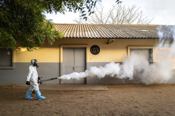 In this Wednesday, April 1, 2020, photo, a municipal worker sprays disinfectant at a school to help curb the spread of the new coronavirus in Dakar, Senegal. The new coronavirus causes mild or moderate symptoms for most people, but for some, especially older adults and people with existing health problems, it can cause more severe illness or death. (AP Photo/Sylvain Cherkaoui)
