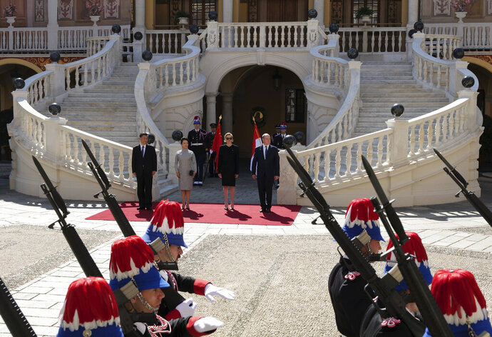 From left to right, Chinese President Xi Jinping, his wife Peng Liyuan, Prince Albert II of Monaco's wife, Princess Charlene and Prince Albert II of Monaco review the honor guards during a welcome ceremony at Monaco Palace, Sunday, March 24, 2019. Xi is paying the first state visit by a Chinese president to the tiny Mediterranean principality of Monaco on Sunday. (AP Photo/Olivier Anrigo)