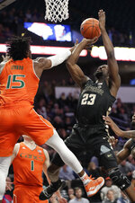 Wake Forest's Chaundee Brown (23) shoots against Miami's Ebuka Izundu (15) during the first half of an NCAA college basketball game in Winston-Salem, N.C., Tuesday, Feb. 26, 2019. (AP Photo/Chuck Burton)