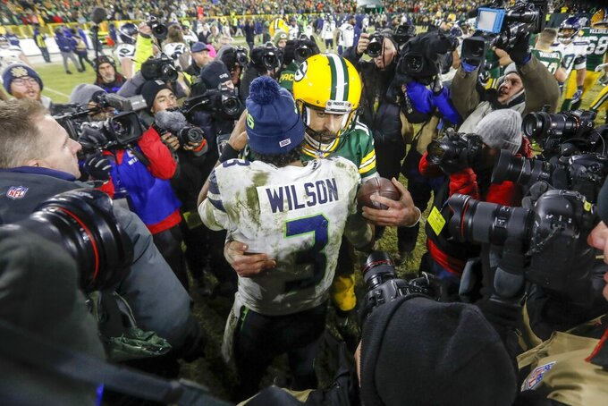 Green Bay Packers' Aaron Rodgers talks to Seattle Seahawks' Russell Wilson after an NFL divisional playoff football game Sunday, Jan. 12, 2020, in Green Bay, Wis. The Packers won 28-23 to advance to the NFC Championship. (AP Photo/Mike Roemer)