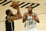 Brooklyn Nets' Kevin Durant, left, shoots against Milwaukee Bucks' Khris Middleton, right,  during the second half of an NBA basketball game Tuesday, May 4, 2021, in Milwaukee. (AP Photo/Aaron Gash)