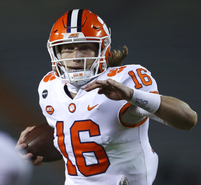 FILE - In this Saturday, Dec. 5, 2020, file photo, Clemson's Trevor Lawrence runs for a touchdown against Virginia Tech during the third quarter of an NCAA college football game in Blacksburg, Va. Lawrence was voted The Associated Press offensive player of the year for the Atlantic Coast Conference and was one of a league-best 10 Clemson selections to the AP all-ACC team. (Matt Gentry/The Roanoke Times via AP, Pool, File)